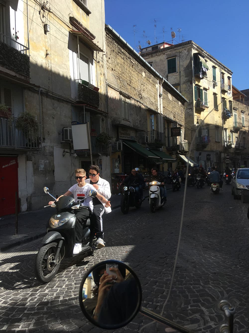 Locals riding around Naples on scooters