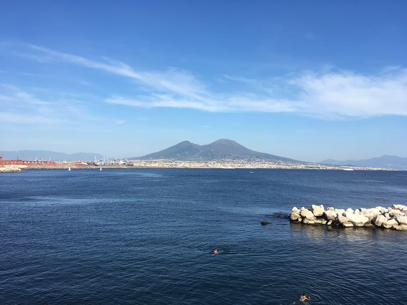 People swimming in the sea under the watch of Vesuvius